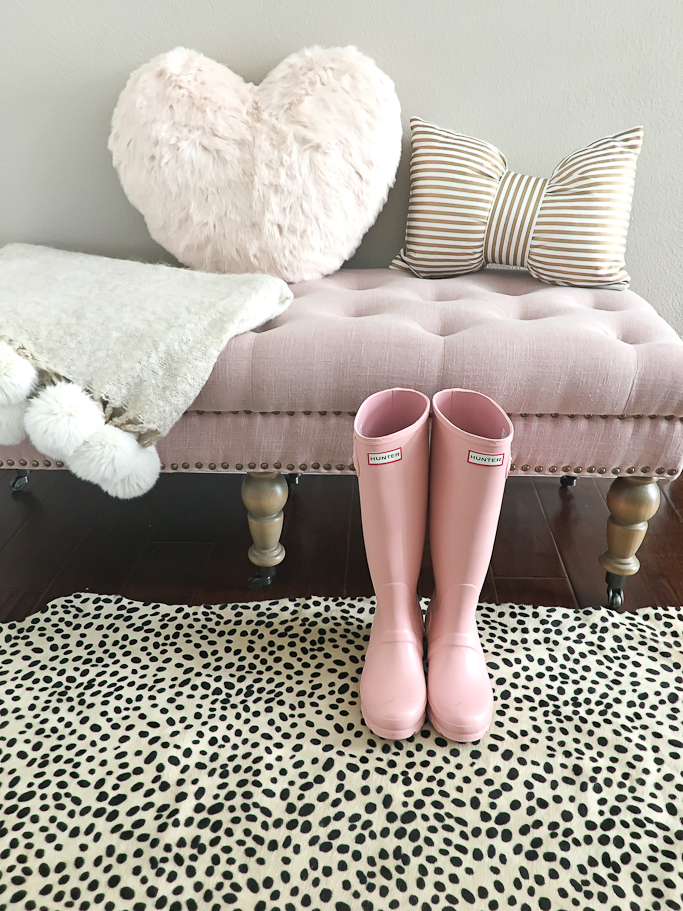 Pink Hunter boots, pink tufted bench, heart pillow, gold striped bow pillow, pom pom throw blanket, cheetah rug