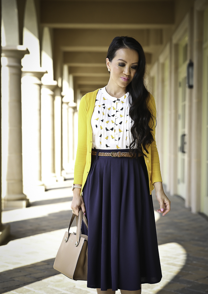 modest work outfit navy pleated skirt mustard cardigan bow pumps